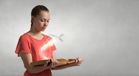 broaden: Young woman in red dress with book in hand and airplane flying from pages