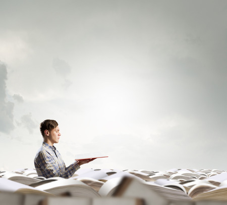 develope: Young handsome man in pile reaching hand with book