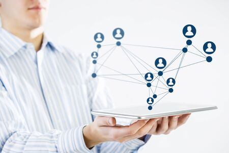 network concept: Close view of businessman holding tablet presenting social network concept