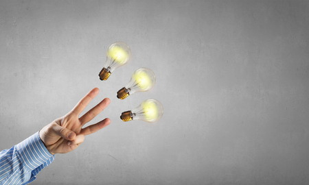 Businessman pointing with finger on glass glowing light bulb on dark background
