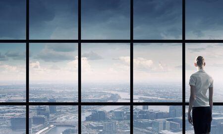 window view: Back view of businesswoman looking in office window