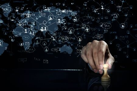 pawn adult: Hand of businessman on dark background making chess move