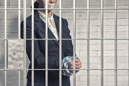 prison: empresaria joven habla en la sala con las manos atadas y cinta adhesiva en la boca