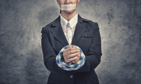 speechless: Young speechless businesswoman with tied hands and adhesive tape on mouth