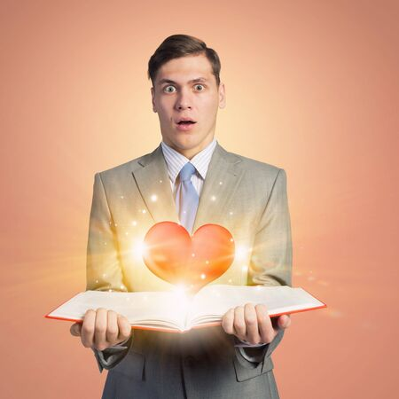 heart intelligence: Young shocked businessman with opened book in hand and red heart on pages