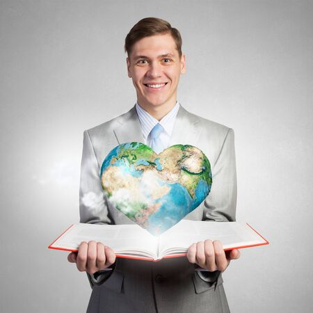 heart intelligence: Young businessman with opened book in hands. Elements of this image are furnished by NASA