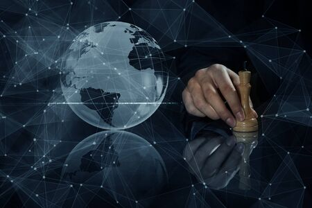 chess move: Hand of businessman on dark background making chess move