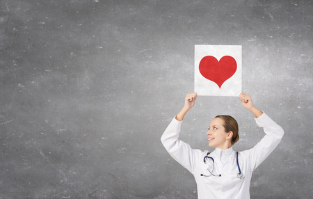 private hospital: Attractive healthcare woman worker with red heart symbol Stock Photo