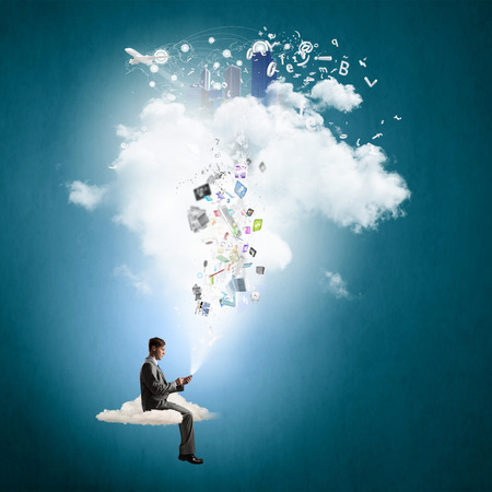 Young businessman sitting on cloud with mobile phone in hands