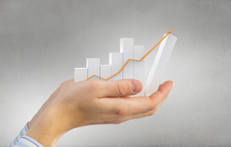 financial growth: Close up of hand holding growing graph arrow