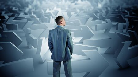 way out: Confused young businessman in labyrinth choosing right way Stock Photo