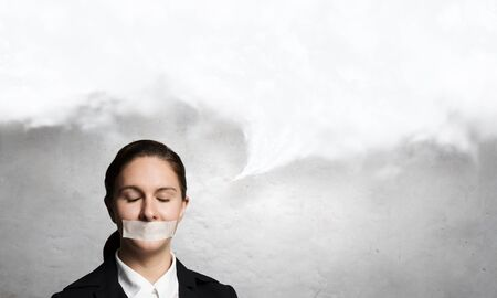 word of mouth: Young speechless businesswoman with adhesive tape on mouth Stock Photo