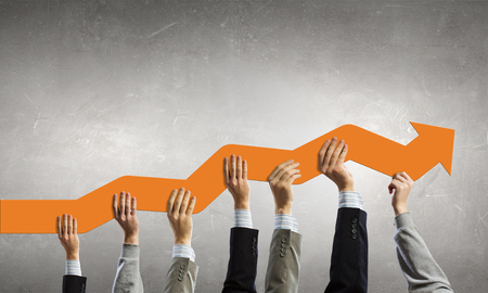 multiple targets: Group of business people holding growing graph in raised hands Stock Photo