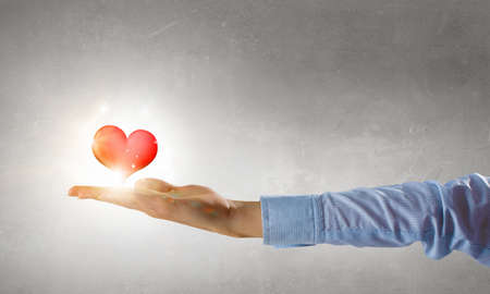 Close up of male hand holding red heart