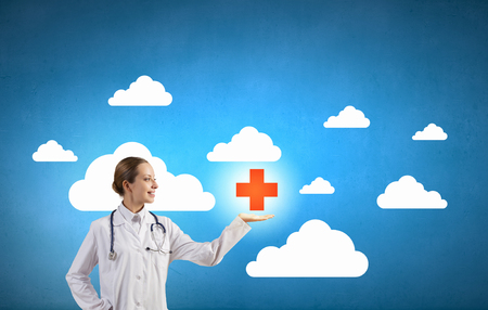 healthcare facilities: Attractive female doctor in white showing medicine cross sign