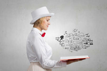broaden: Young woman in white cylinder and red bowtie with book in hands