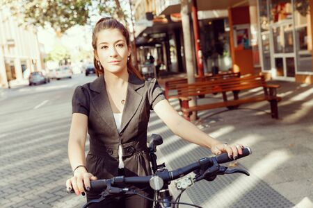 20 25 years: Young woman in business wear commuting on bicycle in city