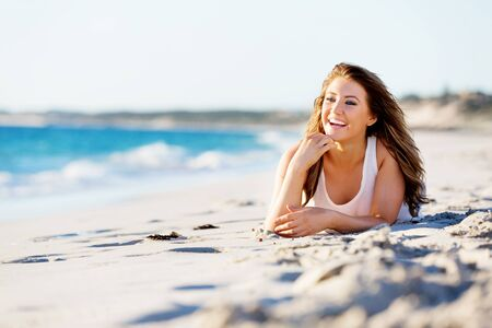 beautiful body: Portrait of young pretty woman relaxing on sandy beach