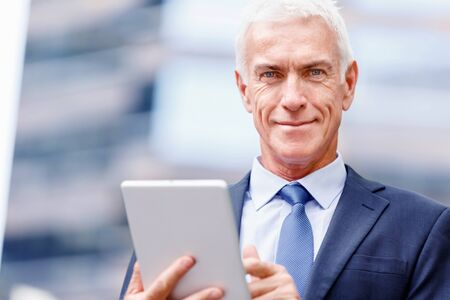 old man standing: Senior businessman holding touchpad outdoors