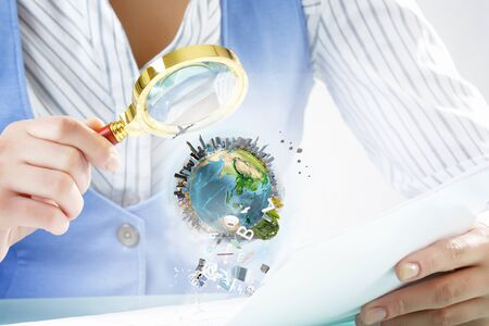 optical people person planet: Close view of businessperson exploring Earth planet with magnifying glass. Elements of this image are furnished by NASA Stock Photo