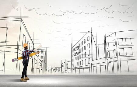 arquitecto: Ingeniero de sexo femenino joven en sombrero duro con el l�piz grande y edificios esboza en el fondo