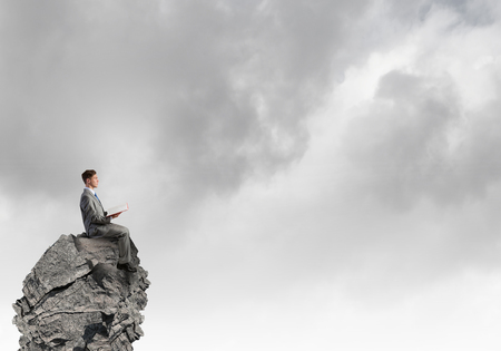 Young businessman sitting on rock top with book in hands