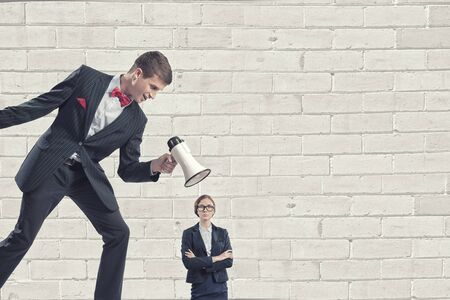 humiliation: Aggressive businessman screaming in megaphone on her colleague Stock Photo