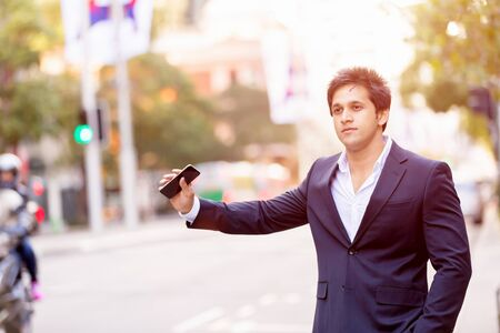 catching taxi: Businessman in suit catching taxi in city with mobile phone in his hands Stock Photo