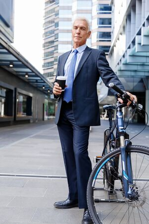 break from work: Successful businessman in suit riding bicycle and holding coffee