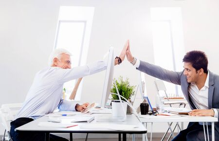 company merger: Businessmen in office cheering at their success