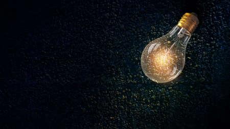 Glass glowing light bulb on stone background
