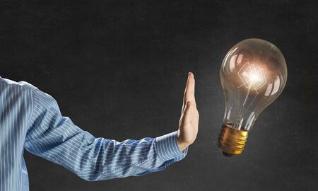 wattage: Businessman hand showing stop gesture and glass glowing light bulb on dark background