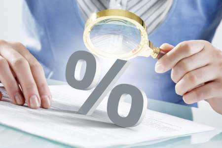 percentage sign: Close view of businesswoman looking at percentage sign with magnifier