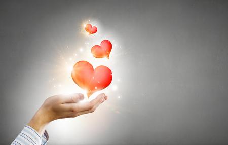 Close-up van handen die rood hart in palmen houden Stockfoto