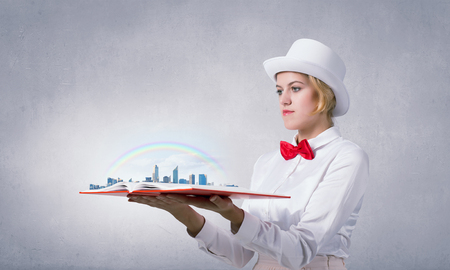 develope: Young woman in white cylinder and red bowtie with book in hands