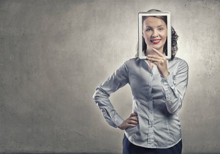 express positivity: Smiling woman holding tablet instead of her face Stock Photo