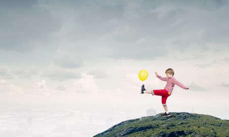 joyfully: Little cute boy playing joyfully with colorful balloon