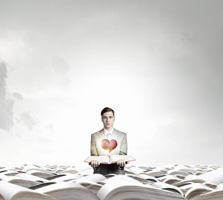 heart intelligence: Young smiling businessman with opened book in hand and red heart on pages