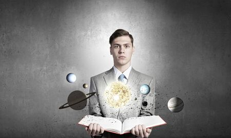 astronomie: Young businessman with book and planets of space spinning around Lizenzfreie Bilder