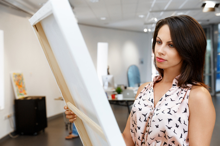 canvas art: Young caucasian woman standing in an art gallery in front of painting displayed on white wall Stock Photo