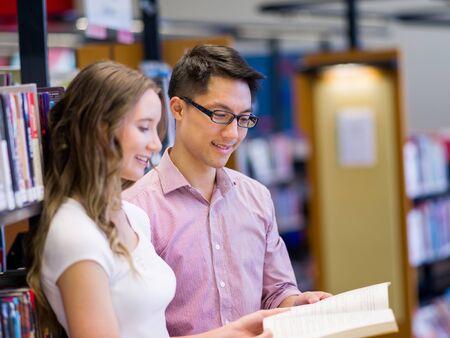 Deux jeunes étudiants travaillant ensemble à la bibliothèque