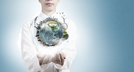 eco tourism: Close up of female doctor holding Earth planet in hands. Elements of this image are furnished by NASA Stock Photo