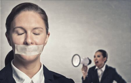 speechless: Young speechless businesswoman with tied hands and adhesive tape on mouth under aggressive pressure Stock Photo