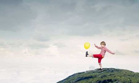 carelessness: Little cute boy playing joyfully with colorful balloon