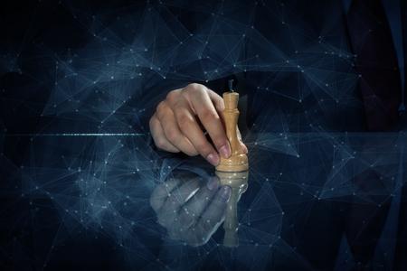 Hand van zakenman op donkere achtergrond die schaakbeweging maken Stockfoto