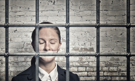 female prisoner: Young speechless businesswoman in ward with tied hands and adhesive tape on mouth Stock Photo