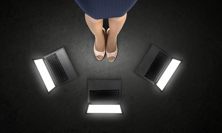Top view of businesswoman feet and laptop on floor