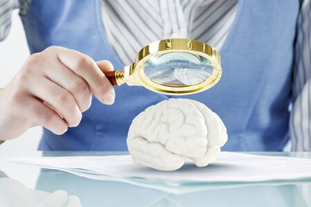 zooming: Close view of woman zooming human brain with magnifying glass