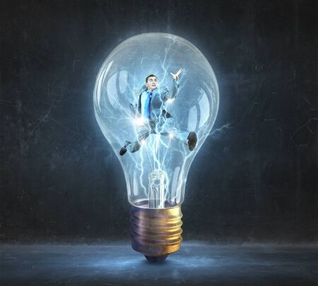 jumping businessman: Jumping businessman inside glass light bulb as brainstorming concept Stock Photo