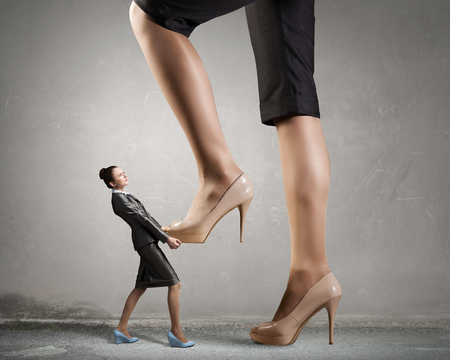 suppressed: Businesswoman foot stepping on tiny businesswoman presenting power concept